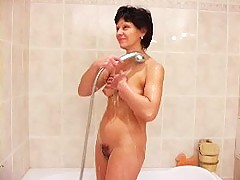 Naughty mommy poses in shower and dildoes herself